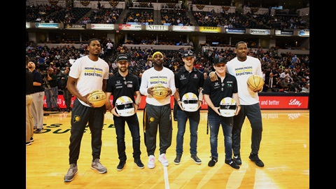 James Hinchcliffe, Alexander Rossi, and Conor Daly exchange helmets with members of the Indiana Pacers during IMS Night With The Pacers at Bankers Life Fieldhouse in Indianapolis, IN